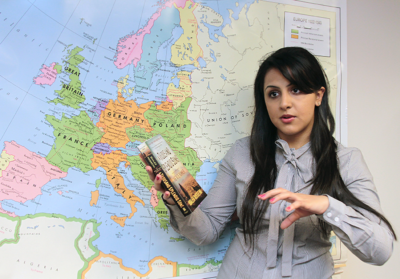 Student talks about a book in front of a map of Europe
